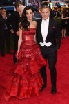 Amal Clooney in a red leather corset & ruffled tiered gown by John Galliano for Margiela & George Clooney at the 2015 Met Gala. 01.