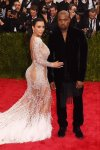 Kim Kardashian in a silver lace & feathered Roberto Cavalli gown & Kanye West at the 2015 Met Gala. 01.
