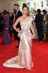 Lizzy Caplan in a single-shoulder draped blush gown with floral embroidery by Donna Karan & a nude pearl Edie Parker clutch at the 2015 Met Gala. 01.