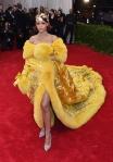 Rihanna in a gold silk & fur couture design from Guo Pei with jewelry by Cartier at the 2015 Met Gala. 01.