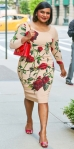 Mindy Kaling in a rose-printed Dolce & Gabbana sheath dress with jewelry by Vita Fede & red d'Orsay pumps on her way to the set of Good Morning America.
