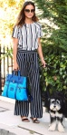 Jamie Chung walked her dog in mixed sblack & white striped separates with a blue bag, oversize sunglasses, & flat sandals.