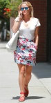 Reese Witherspoon's street style is on point in a white tee with a floral print lace scalloped skirt, red flat strappy sandals, & canvas tote.