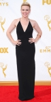 Kate McKinnon in a black Badgley Mischka halter dress with a gold bangle.