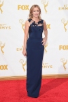 Kim DIckens in a navy blue embellished column gown.