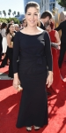 Mayim Bialik in a black long sleeved belted gown.