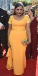 Mindy Kaling in a yellow belted short sleeved gown with an Edie Parker clutch.
